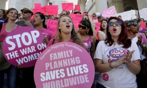 Planned Parenthood supporters rally for women's access to reproductive health care on National Pink Out Day at Los Angeles City Hall. Without free contraception and access to abortion, pregnancies are estimated to increase, leading to widespread health problems.