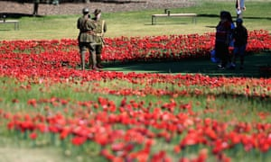 Soldiers stand amoungst a field of fabric poppies ahead of the Remembrance Day Service at the Australian War Memorial on November 11, 2018 in Canberra.