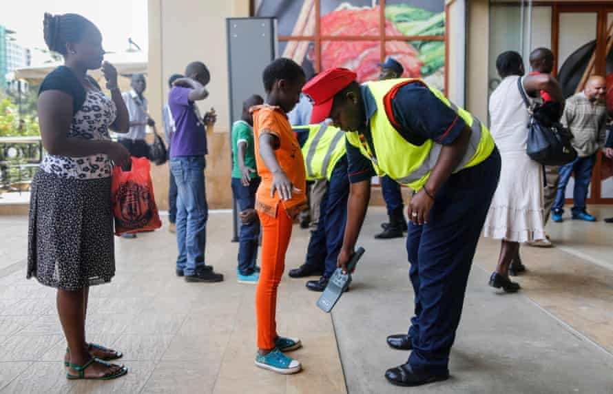 Shoppers are inspected with a metal detector as they enter the Westage Mall in Nairobi