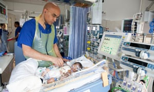 A nurse attends to two-week-old baby Mason.