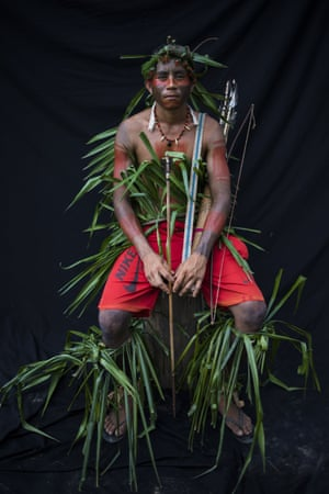 Ronilson Tembe, 28, poses for a portrait during a meeting of the Tembe tribes in the Tekohaw village, in the Alto Rio Guama Indigenous Reserve, in Brazil's Para state. Tembe warriors wear colorful headdresses of macaw and other feathers, and wield bow and arrows that they use to hunt and to protect their homeland, which is constantly under threat in the globally vital Amazon region