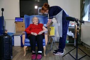Annie Innes, 90, gets ready to receive a Covid-19 vaccine at a care home in Hamilton, Scotland