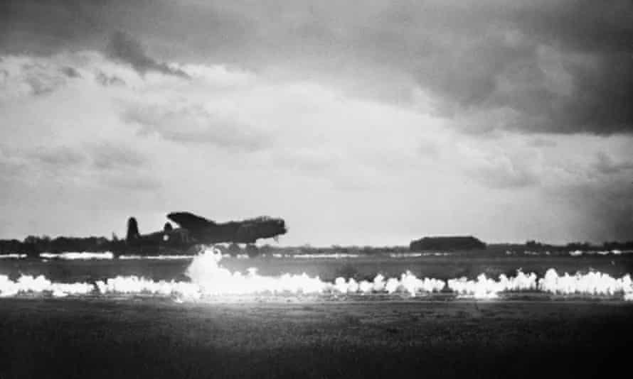An Avro Lancaster of the RAF's No 35 Squadron takes off with Fido petrol burners on either side of the runway at Graveley, Huntingdonshire in May 1945.