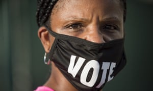 Caprice Clipps wears a 'vote' mask as she waits outside the Smoothie King Center in New Orleans for one of the last days of early voting in the US presidential elections.
