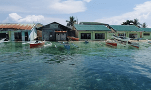 On Bilangbilangan island homes are inundated, gardens submerged, and schoolchildren sit in classrooms ankle-deep in water.