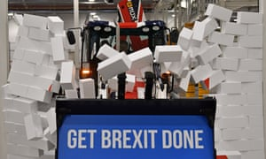 Boris Johnson drives a JCB through a symbolic wall during a campaign event at a JCB factory in Staffordshire