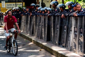 Caracas, VenezuelaA man rides his bicycle as policemen stand on the sidewalk before a demonstration called by union leaders to demand labour protection against dismissals of civil servants . The demonstration was finally called off due to the large deployment of security forces in the streets