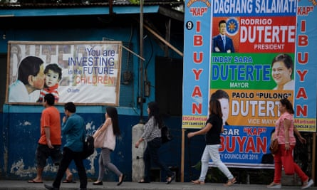 People walking past Duterte ads in Davao City, the Philippines