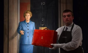 A Christie's employee holds Margaret Thatcher's red dispatch box which had a guide price of £3,000-£5,000, in front of a painting by artist Michael Noakes.