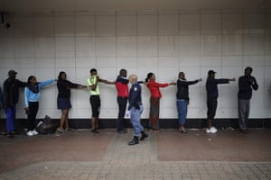 A member of the South African Police Service (SAPS) enforces social distancing as he makes shoppers hold their hands out in front of them to ensure that they are at least one metre apart from one another while they queue outside a supermarket in Yeoville.