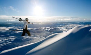Skiing in Åre, the largest winter sports resort in Sweden. A man holding his skis on his shoulder walks through deep powder snow.