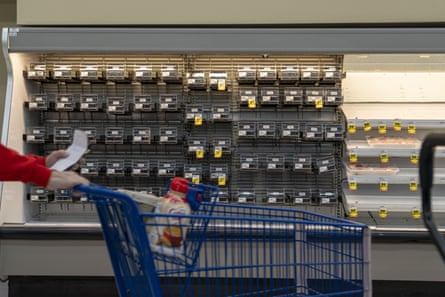 A customer pushes a shopping cart past empty shelves at a grocery store in Dayton, Ohio,