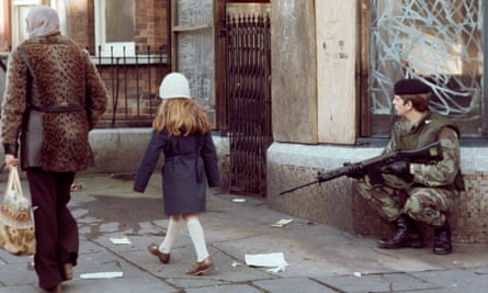 Civilians walk past a British soldier on patrol in the republican New Lodge district of Belfast in 1978 … 'The only time you'd call the police in my area would be if you were going to shoot them'