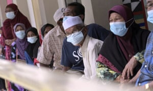 Voters wearing face masks wait at a polling station during a state election in Sabah on Borneo island, on Saturday.