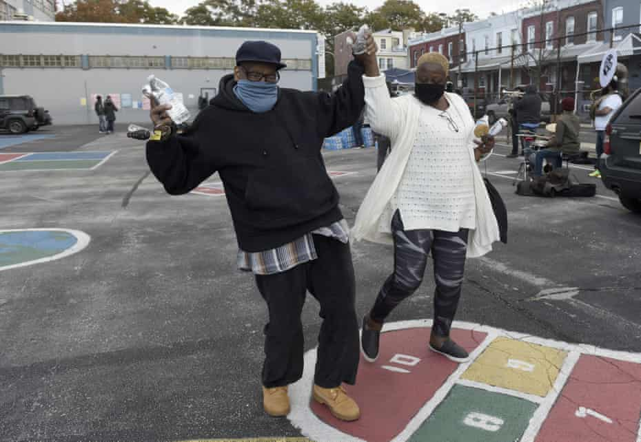 Louis Harris, left, and his wife Jean dance in the parking lot of their voting site on Tuesday in Philadelphia.
