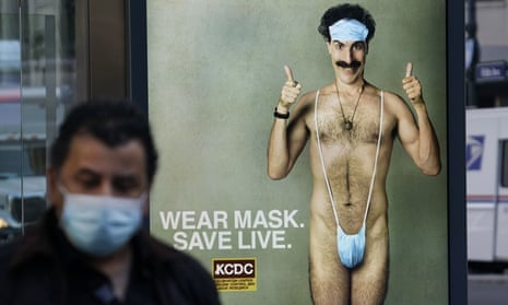 A person wearing a mask walks past a bus stop ad for the Borat 2 in New York City