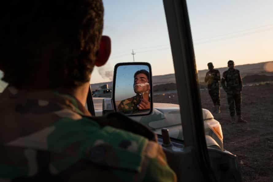 A Peshmerga shaves on the side of the Hawler - Kirkuk road after his unit fled Kirkuk.