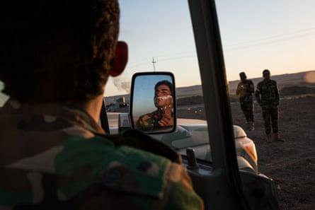 A Peshmerga shaves on the side of the Hawler - Kirkuk road after his unit fled Kirkuk.