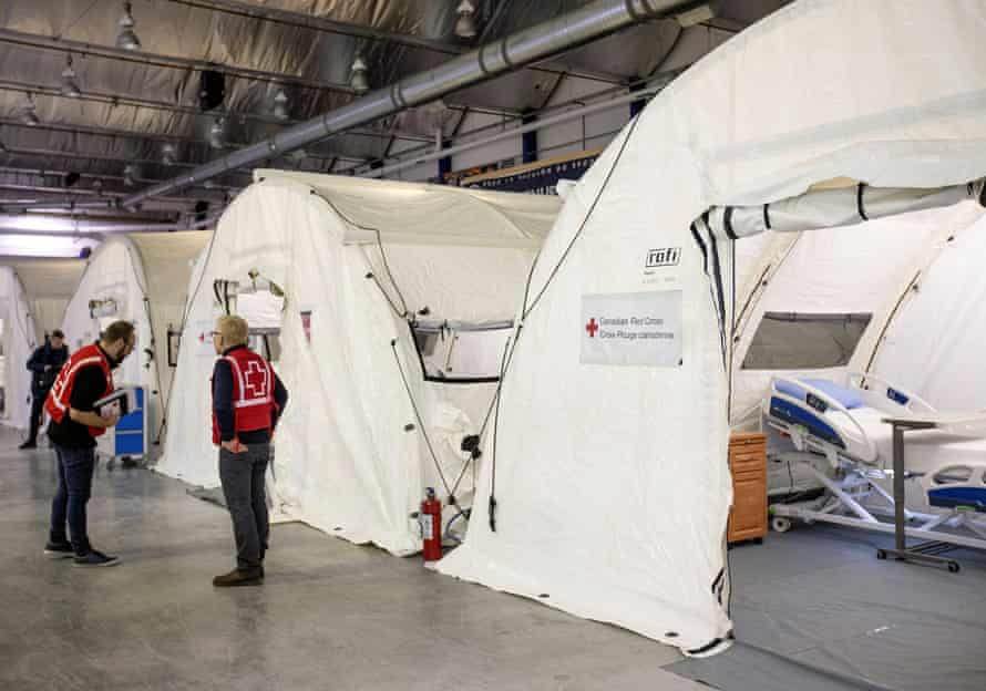 Volunteers are seen at a mobile hospital set up in partnership with the Canadian Red Cross in the Jacques-Lemaire Arena to help care for patients with the coronavirus in Montreal on Sunday.