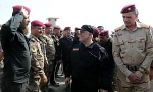 The Iraqi prime minister, Haider al-Abadi, centre, greeting army officers upon his arrival in Mosul.