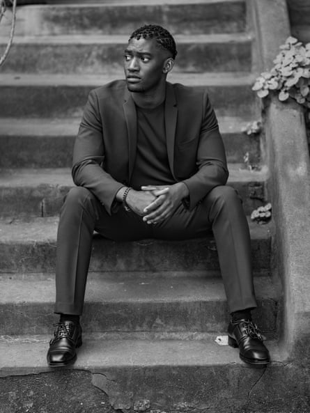 Malachi Kirby, who plays Darcus Howe, sitting on some steps.