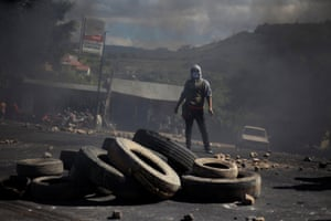 A supporter of Salvador Nasralla, presidential candidate for the Opposition Alliance Against the Dictatorship, stands near a burning barricade during a protest over the delayed vote count for the presidential election in Tegucigalpa, Honduras.