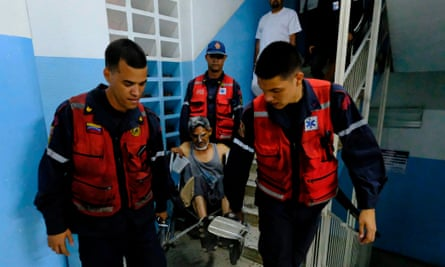 An injured man is carried by paramedics inside Miguel Perez Carreno hospital in Caracas during the worst power outage in Venezuela's history.
