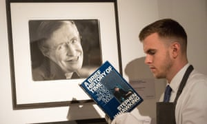An auctioneer assistant reads late physicist Stephen Hawking's seminal works.