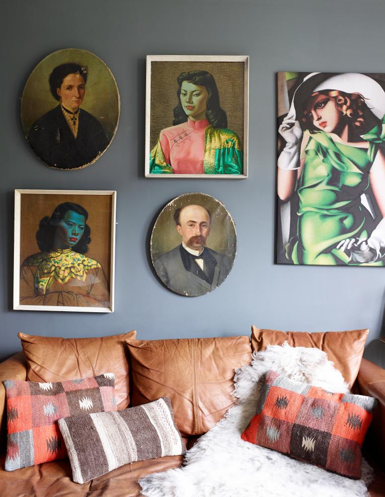 A collection of framed pictures of figures on a dark grey wall and a brown leather sofa and cushions beneath
