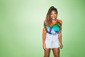 Clara Amfo in brightly coloured top against green background.