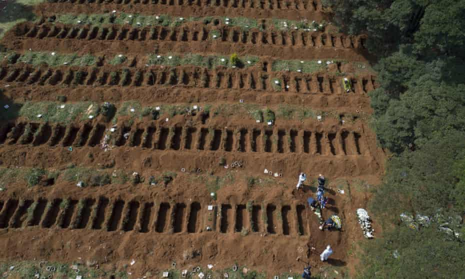 Workers in protective gear bury a person alongside rows of freshly dug graves at the Vila Formosa cemetery in Sao Paulo, Brazil