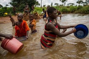Burundian refugees collect water in a river on the edge of Nyarugusu camp