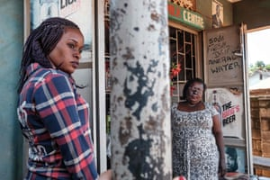 Linette Kirungi (left) and Jennifer Mutesi (right), outside Jennifer's shop in Kampala. Lynette is a programme officer at End Acid Violence Uganda. She pays regular home visits to other acid attack survivors to connect, guide and help them cope with the trauma that comes after being attacked.