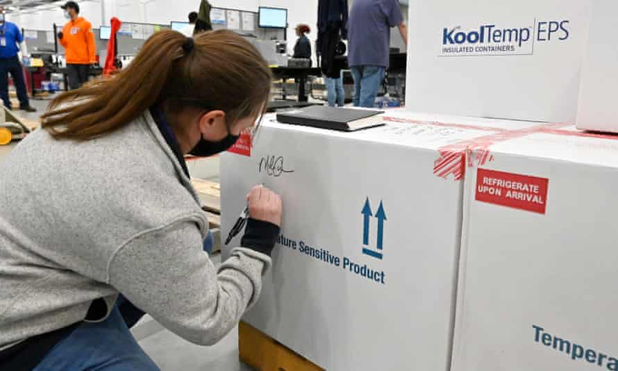 Melissa Owens, operations plant manager for the McKesson Corporation, signs the first shipping box of the Johnson and Johnson Covid-19 vaccine in Shepherdsville, Kentucky, on Monday.