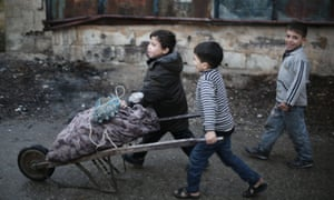 Children push a barrow filled with firewood in Ghouta, Syria