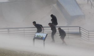 Boys try to take cover during heavy winds blowing sand onto the Bondi Beach promenade during heavy storms in Sydney, Australia, 21 April 2015. More than 20 people have been rescued from floodwaters and 215,000 homes and businesses are without power as storms continue to lash South Eastern Australia.