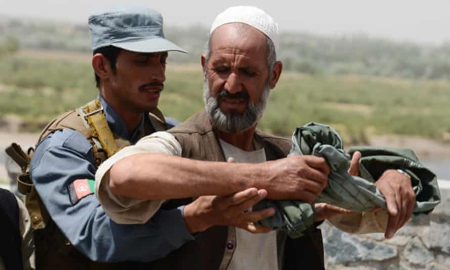 An Afghan policeman searches a man at a checkpoint in Herat province