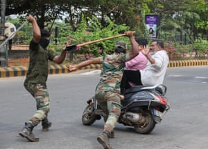 Mangalore, India Members of the Karnataka reserve police force swing their sticks at two men on a scooter who rode too close to a barricade, amid heightened security caused by protests against India's new citizenship law