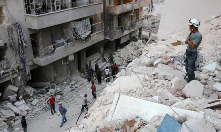 A Syrian civil defence volunteer stands on the rubble of destroyed buildings following an airstrike on eastern Aleppo this month