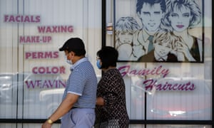 A couple walk by a closed hair salon in Los Angeles on Tuesday. Unless lawmakers step in, the $600 weekly payment will expire on 31 July.