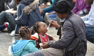 A migrant woman feeds a child after they disembarked from the HMS Bulwark at Catania harbour, Italy, on 8 June.