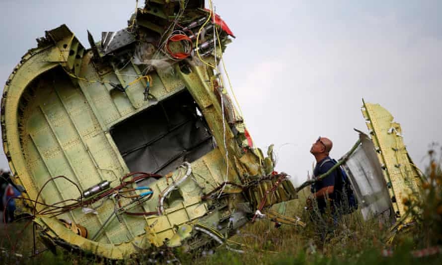 A Malaysian air crash investigator inspecting the crash site.