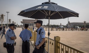 Chinese policemen stand guard on the Tiananmen Square in Beijing, China