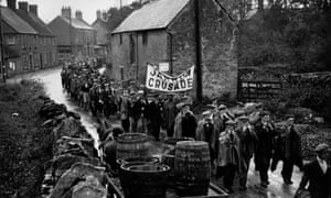 The Jarrow marchers pass through the village of Lavendon, near Bedford, in October 1936. Two hundred men walked the 291 miles from Tyneside to London to deliver a petition for jobs to the government