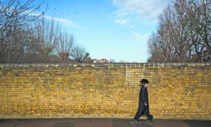 Boy walking in front of wall