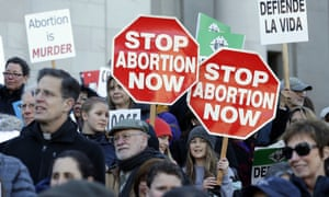 Participants hold signs at an anti-abortion rally. Trump's 'gag rule' executive order could put $9.4bn in US health aid at risk, campaigners say.