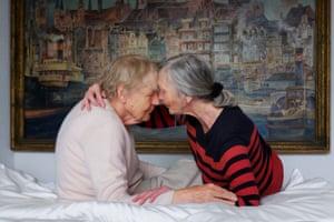 Two older women rub heads in bed