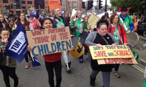 parents and children march with placards