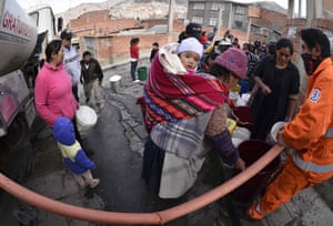 Water from a tanker is rationed for free in a neighbourhood of La Paz