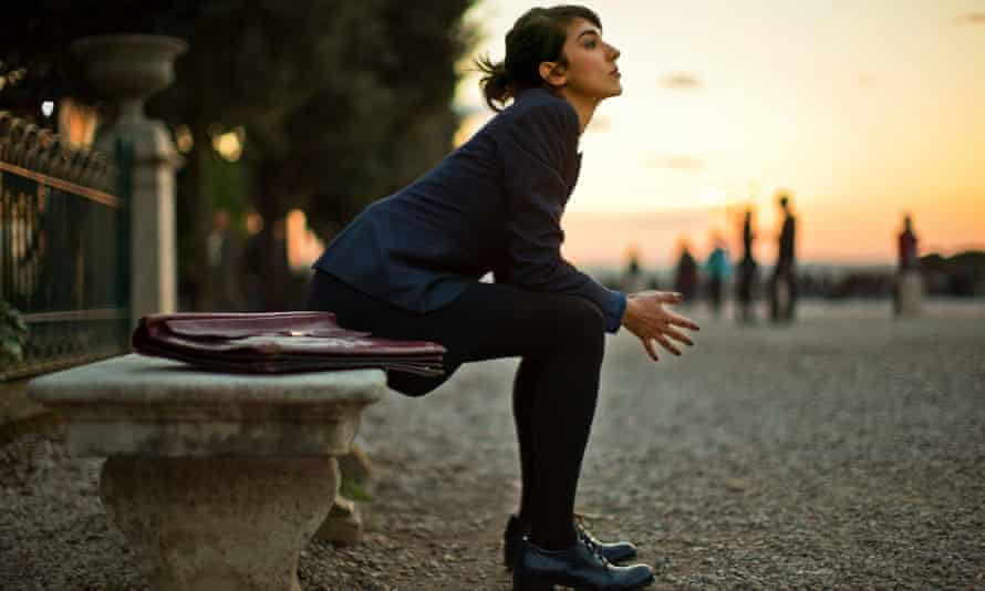 Pensive young businesswoman sitting on a stone bench at sunset